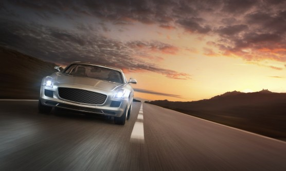 Luxury sports car speeding on a highway at the sunset